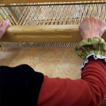 編み機に横糸を通して一本ずつ編んでいきます。